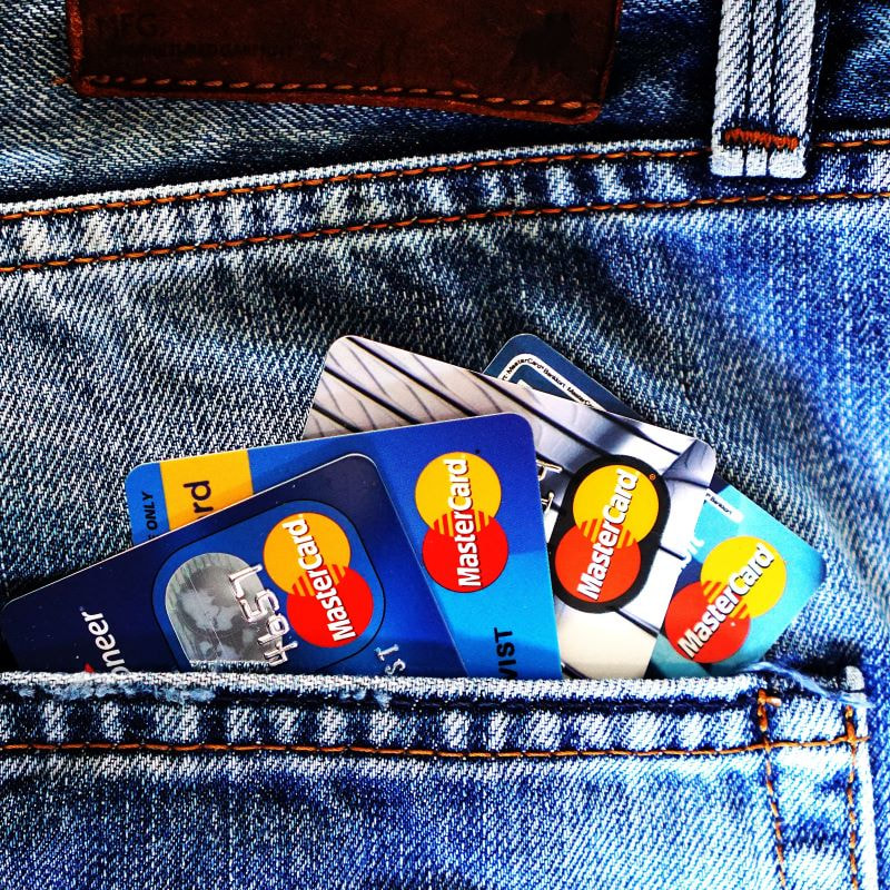 Person holding credit cards in back pocket